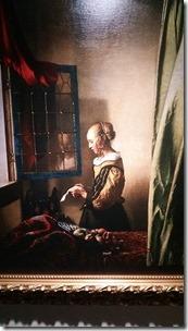 窓辺で手紙を読む女